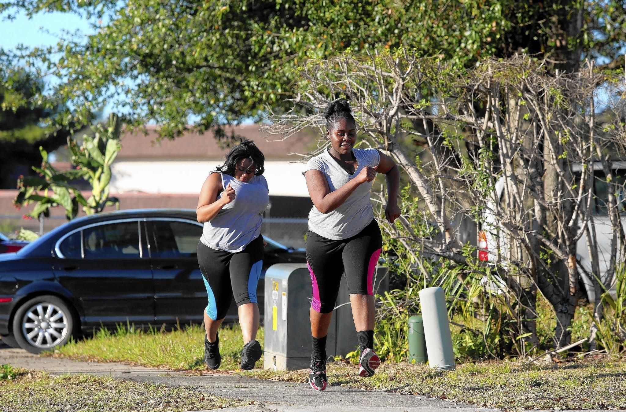 Chellia Cincois, 24, accompanies her sister Julie Phicien, for a jog outside the family's Orlando home, on Monday, February 10, 2014.