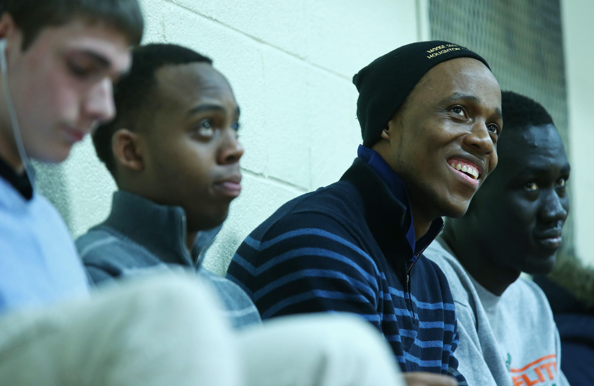 Mooseheart High School student Rodrigue Makindu, second from right, sits in the bleachers with friends before a playoff basketball game between Mooseheart and Serena High School at Somonauk High School.