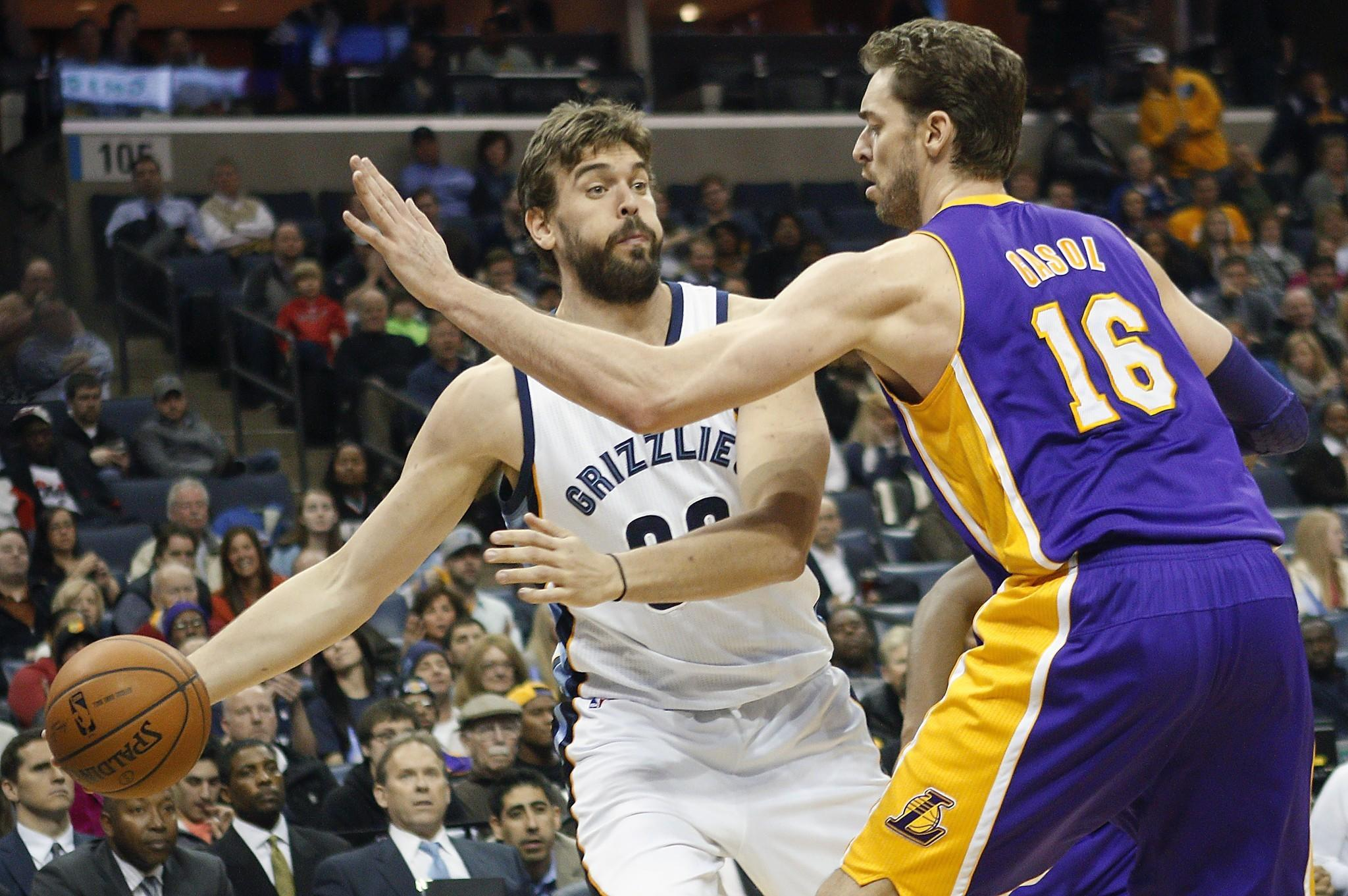 Grizzlies center Marc Gasol tries to pass around his brother, Lakers forward Pau Gasol. While the Grizzlies are still alive in the playoff race, the Lakers have been eliminated.