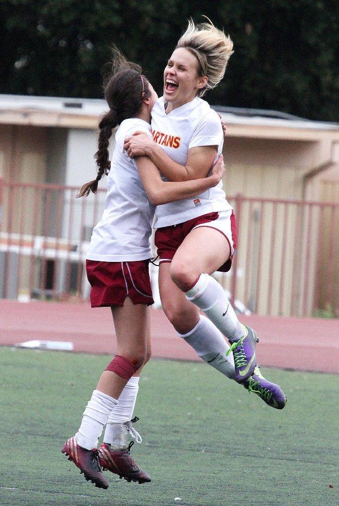La Cañada High's Megan Decker jumps into the arms of teammate Natalie Ragusa after a goal against California in a CIF SS-Division V second-round girls' soccer playoff contest at La Cañada on Wednesday. La Cañada won the game 2-0. (Tim Berger/Staff Photographer)