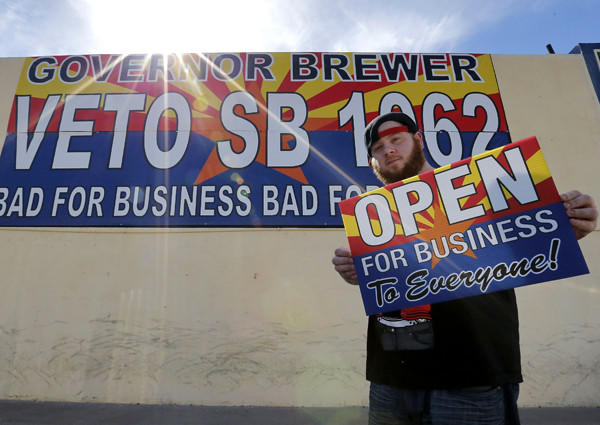 Josh Deinert, a graphic designer, shows a sign opposing Arizona Senate Bill 1062, which was vetoed Wednesday by Gov. Jan Brewer.