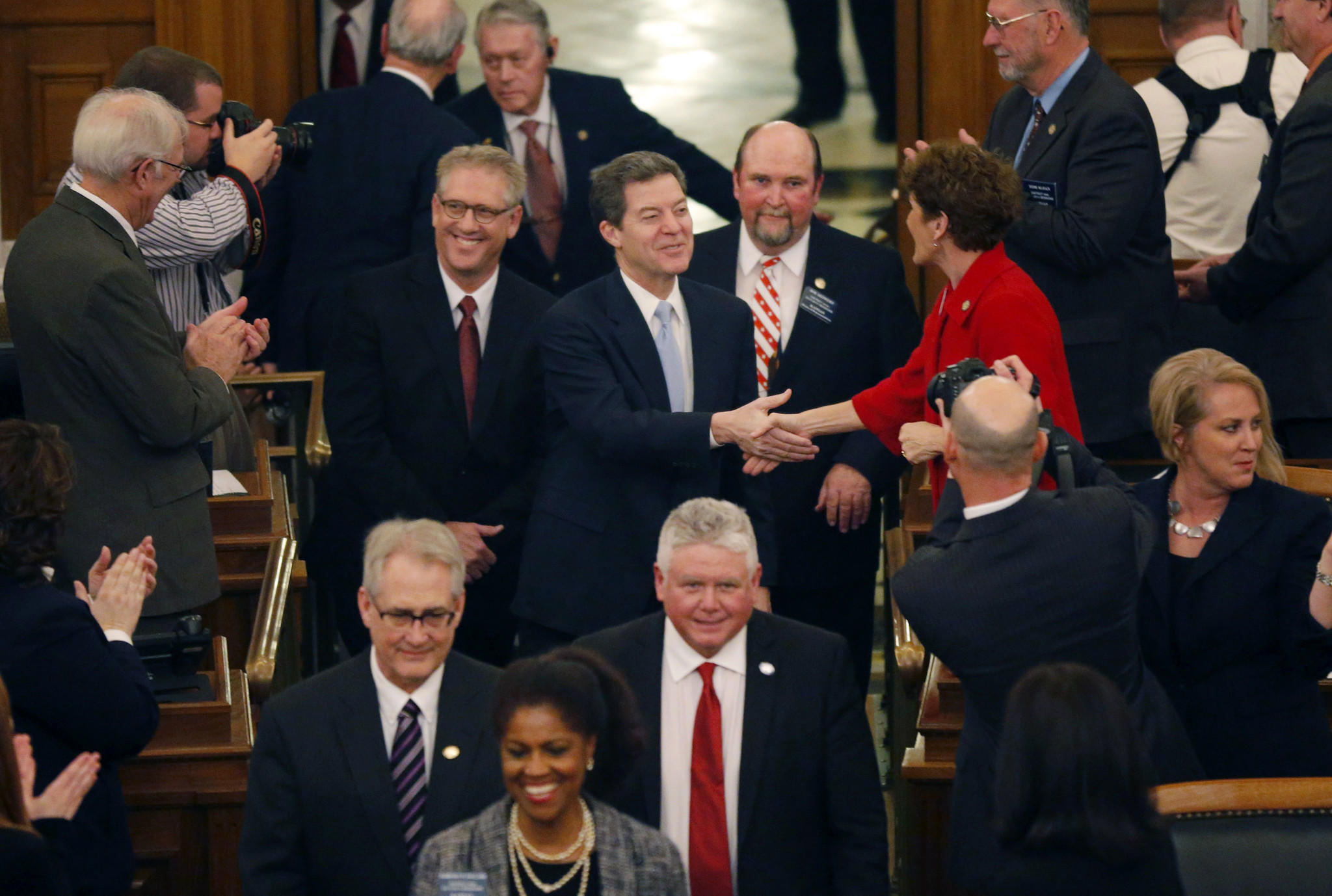 Kansas Gov. Sam Brownback greets representatives before his State of the State speech to an annual joint session of the House and Senate at the Statehouse in Topeka, Kan. Brownback told Kansas legislators that the tax cuts he championed will spur economic growth.