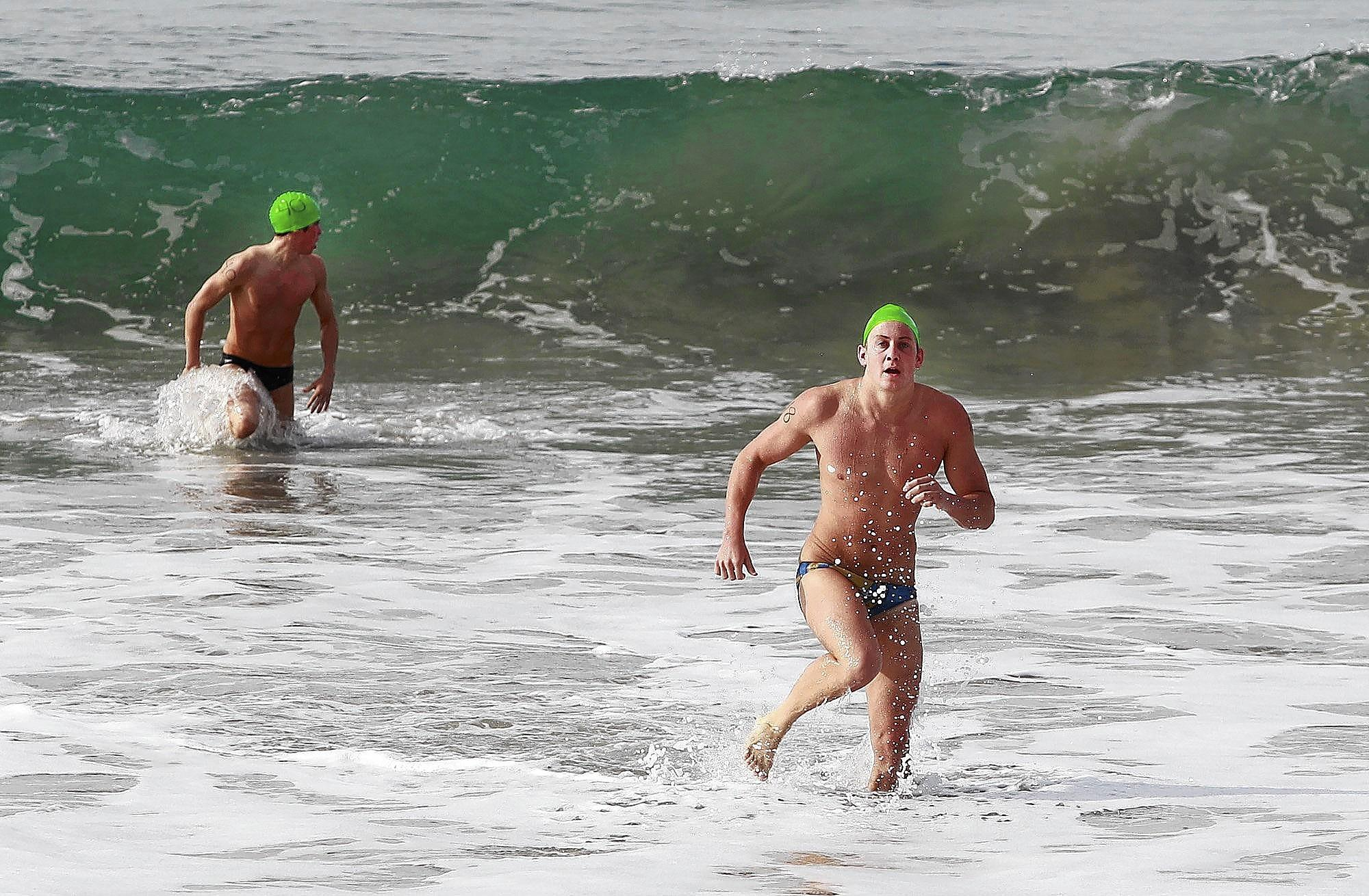 Russell Taylor, right, of Laguna Hills, is first to hit the shore after he completed the 1,000-meter swim to Bird Rock and back in the required 20 minutes during Laguna Beach lifeguard tryouts at Main Beach on Saturday.