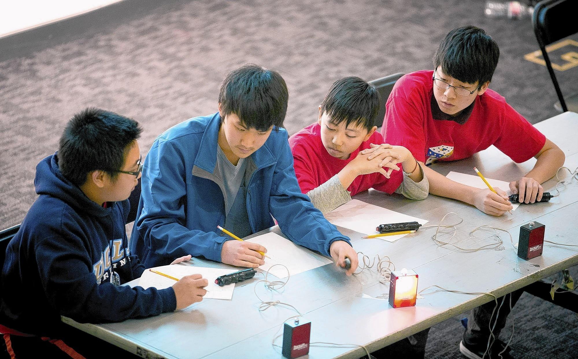 La Cañada High School sophomore William Fu, left, sophomore Colin Um and freshmen Albert Zhai and Daniel Oh work out a problem at the 27th Annual High School Mathematics Competition on Saturday, Feb. 8 at Westmont College in Santa Barbara. The LCHS team dominated the Math Bowl, a team event, for an overall win.