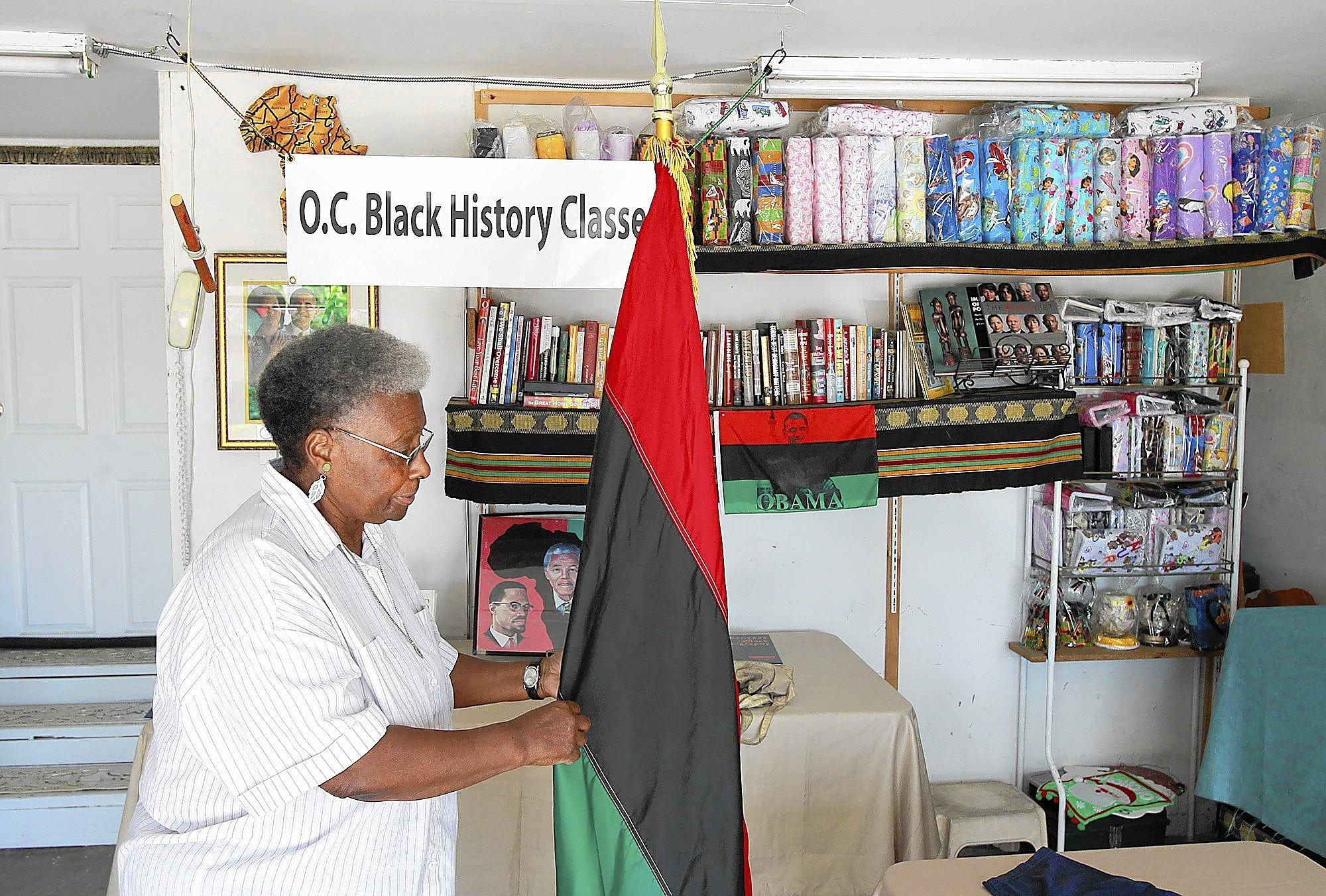Instructor Bea Jones puts up a Universal African flag with green, black and red colors in the garage of Barbara Junious, where the two organize and lecture on Black History two times a month. They are looking for a permanent location so they can teach a wider audience.