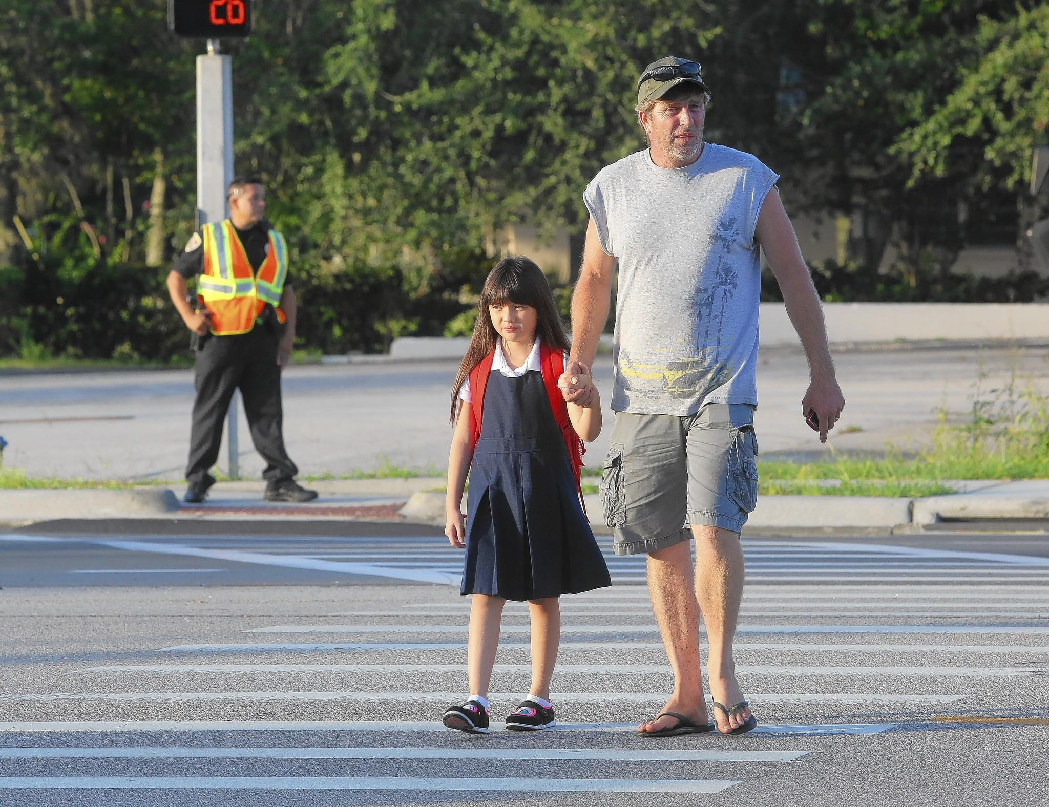 Mike Hayden walks his daughter Destin, 7, across SR 50 on their way to Clermont Elementary in August.