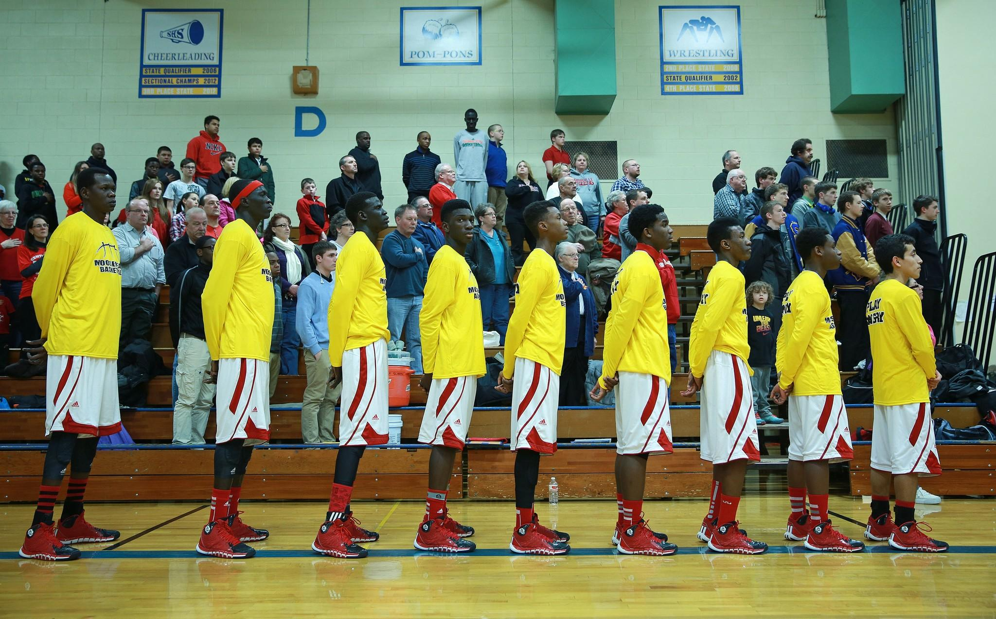 The Mooseheart High School basketball team stands for the national anthem before a playoff game against Serena High School at Somonauk High School on Feb. 26.