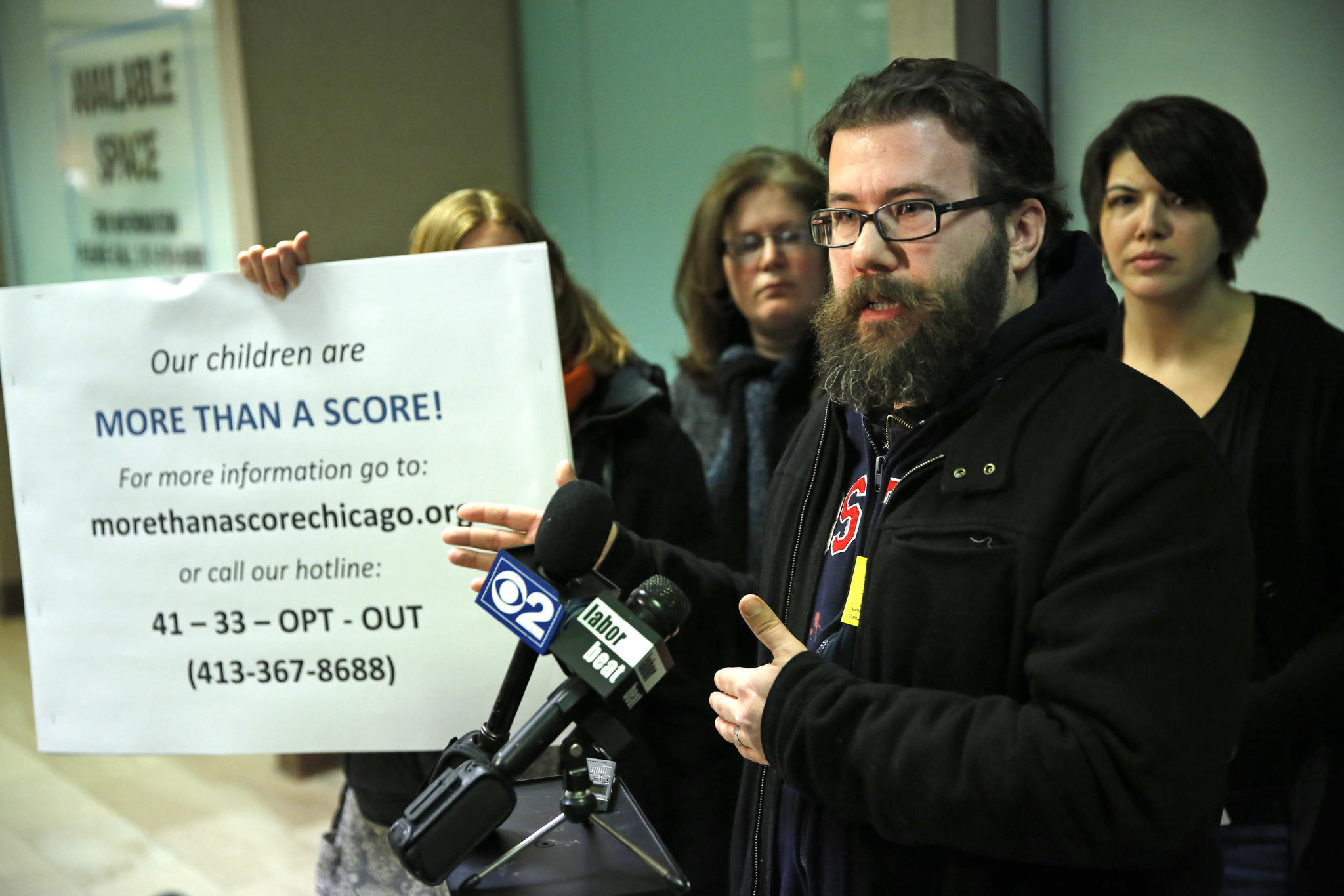 Chris Barrett (R), who has two boys that attend Drummond Montessori Magnet School, speaks about boycotting the Illinois Standards Achievement Test (ISAT) seen here outside of the lobby of Chicago Public Schools headquarters on Feb. 24.