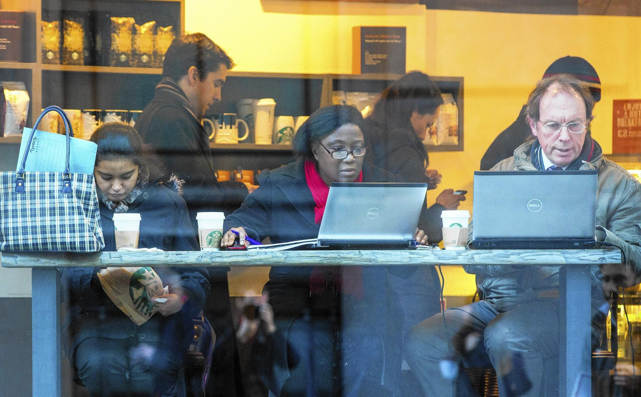 Customers concentrate on their laptops at a Starbucks in London recently.