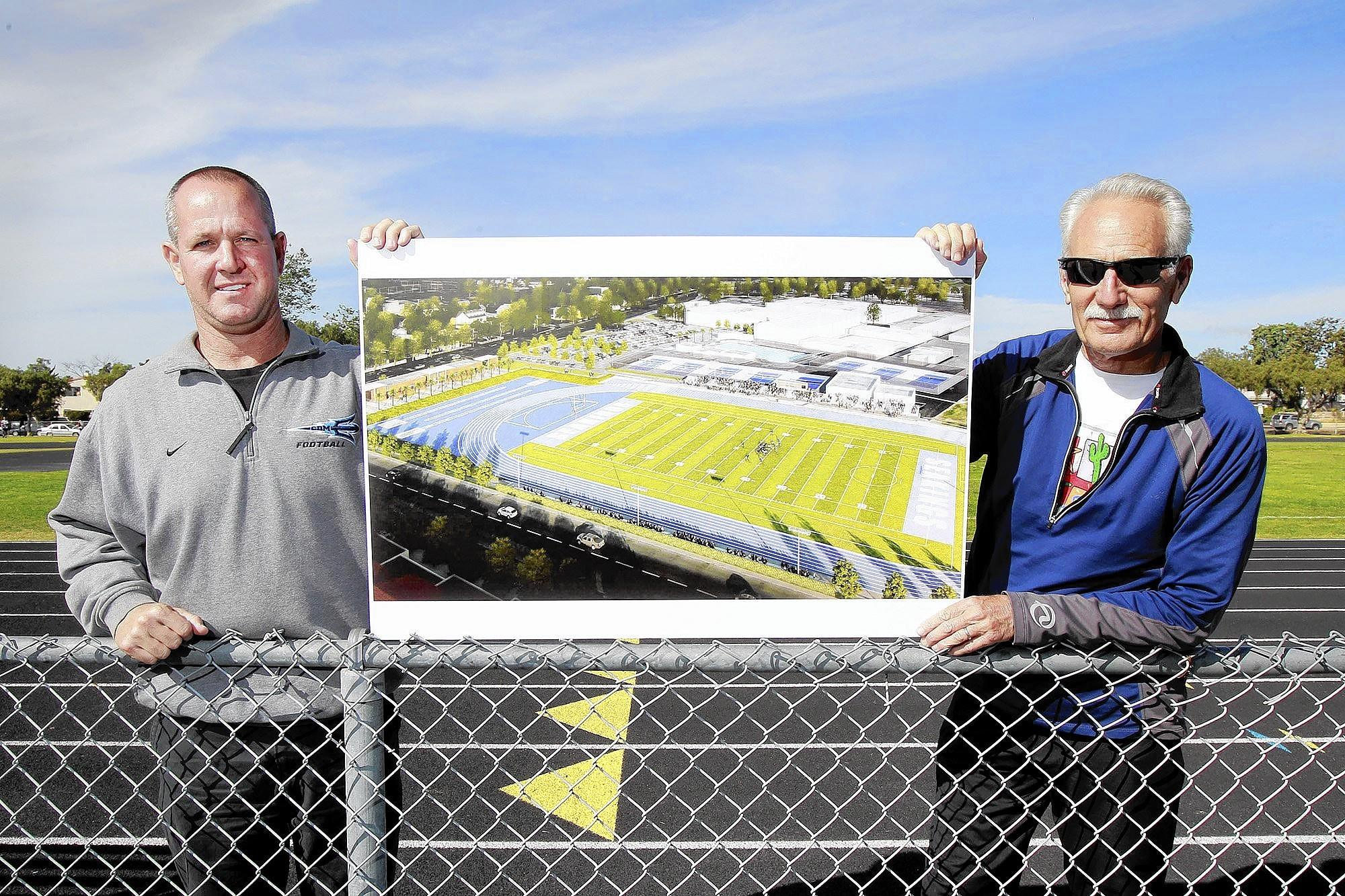 Corona del Mar football Coach Scott Meyers, left, and track and field Coach Bill Sumner, hold a rendering of the proposed stadium at Corona del Mar High School.