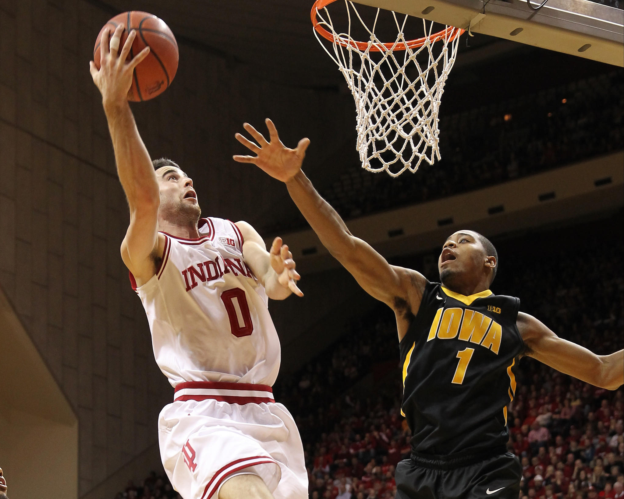 Indiana's Will Sheehey drives to the basket with Iowa's Melsahn Basabe defending during the first half at Assembly Hall.