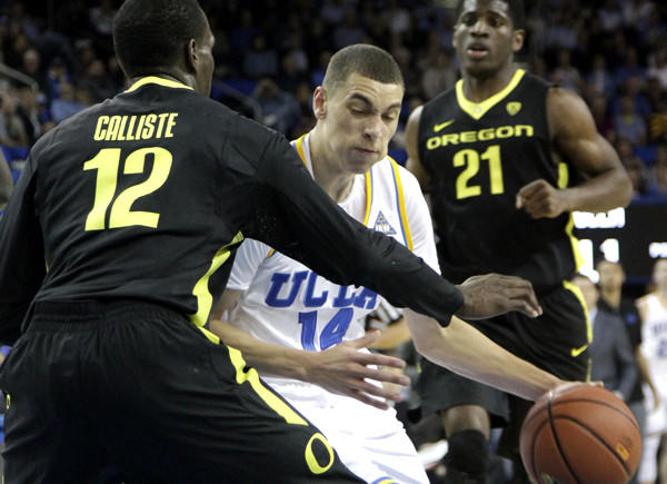 UCLA guard Zach LaVine tries to drive around Ducks guard Jason Calliste in the first half Thursday night at Pauley Pavilion.