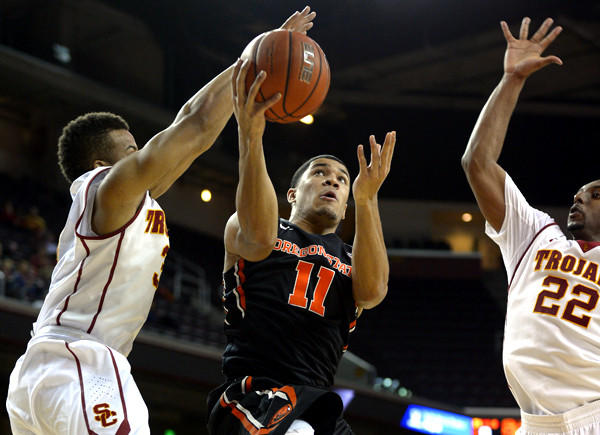 Oregon State guard Malcolm Duvivier (11) has his driving layup challenged by USC guards Chass Bryan and Byron Wesley (22) in the first half Thursday night at the Galen Center.