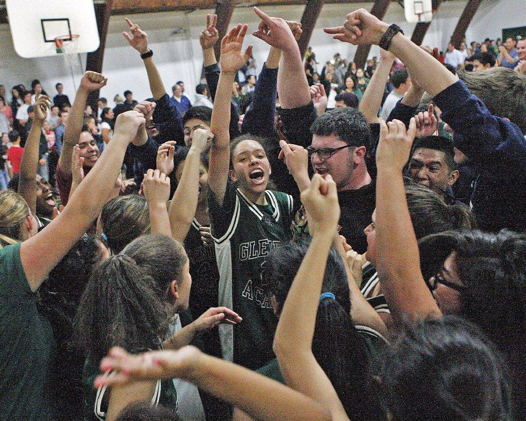 Glendale Adventist Academy's Madison Federicci, in the middle, is surrounded by teammates and fans after beating St. Monica Academy in a CIF-SS Division VI girls' basketball quarterfinal playoff game on Thursday. (Tim Berger/Staff Photographer)