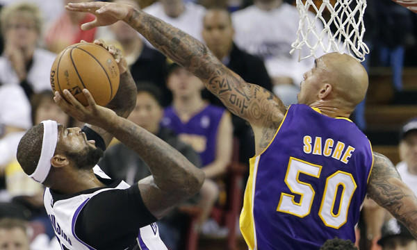 Lakers center Robert Sacre right, tries to block the shot of Sacramento Kings center DeMarcus Cousins during a game on Dec. 6.
