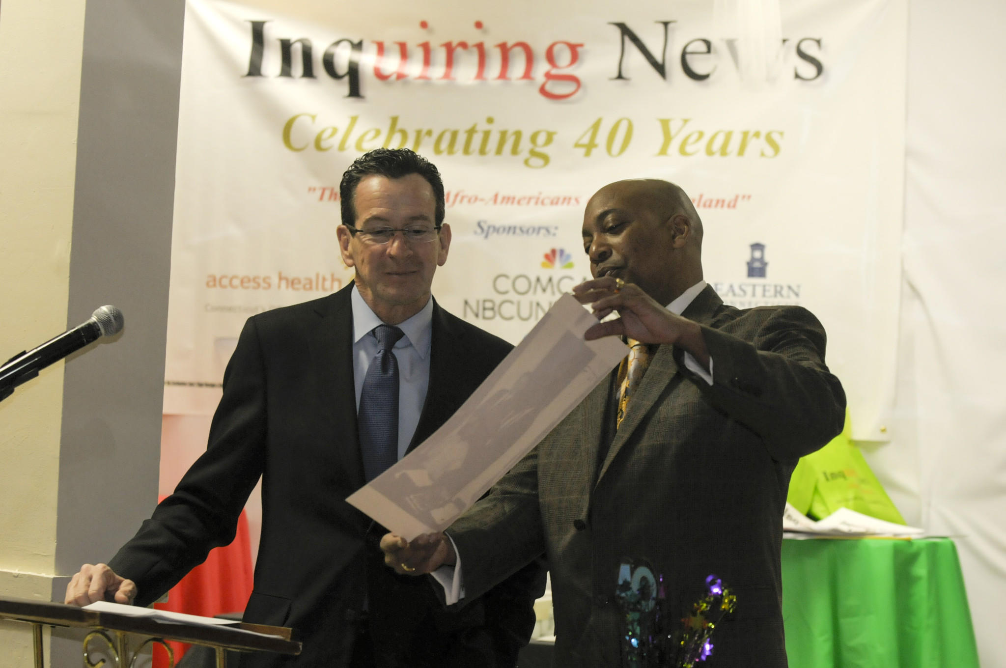 Reggie Hales (at right), the publisher of the Inquiring News in Hartford's north end, shows Gov. Dannel P. Malloy a photograph from the early days of the weekly tab.
