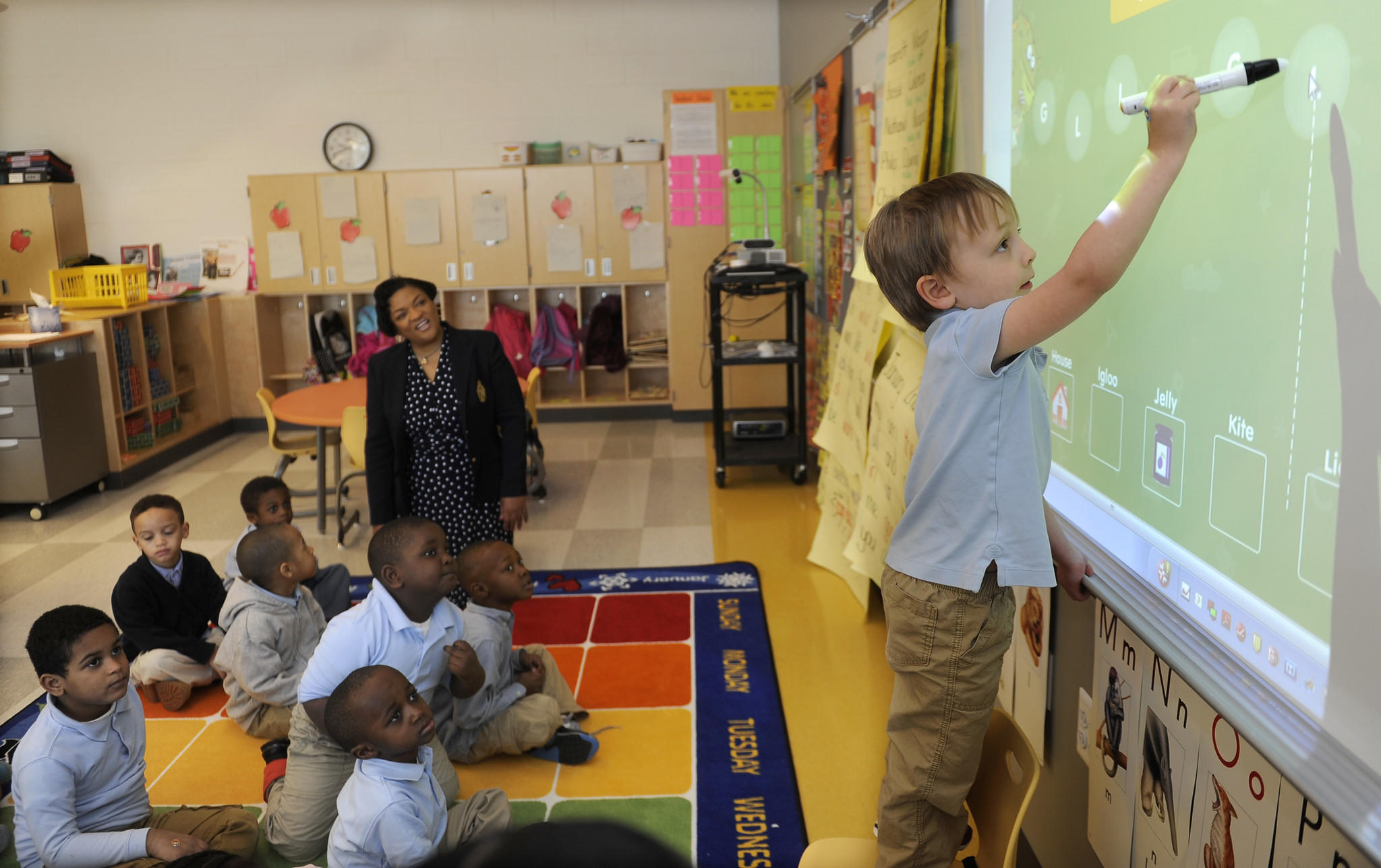 Pre-K student August Green uses a white board to identify letters in his classroom. Principal Amanda Rice is sitting in background with students.
