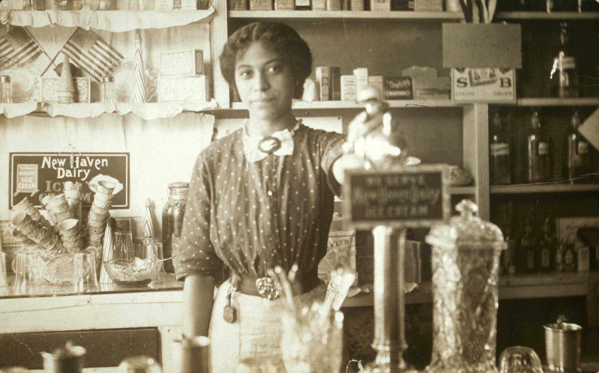 Anna Louise James at soda fountain where she was pharmacist and owner, Old Saybrook, c. 1909-1911.