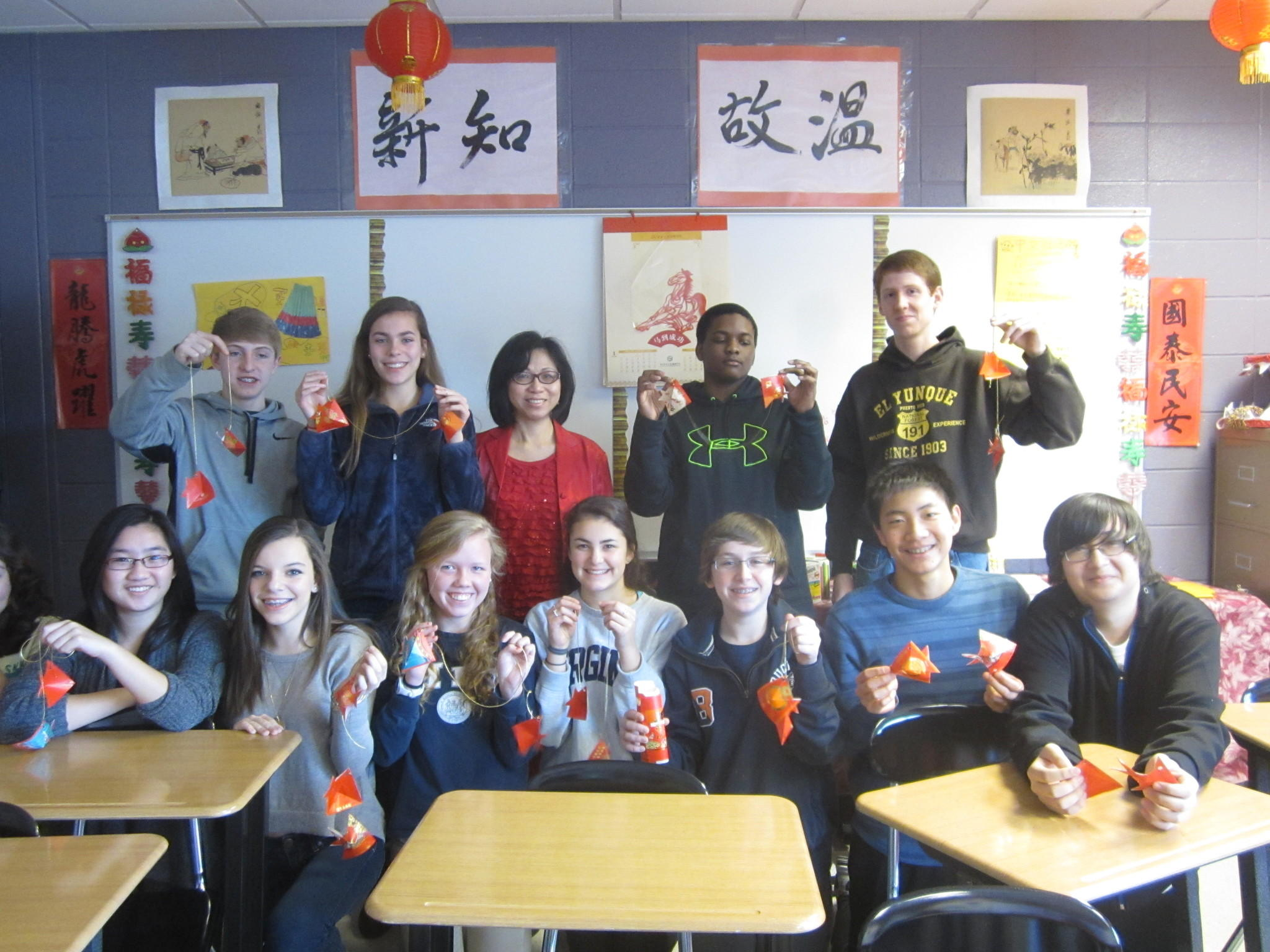 Wendy Richard, top row, third from left, stands with Simsbury's Chinese 2 students as they hold up their paper folding samples.