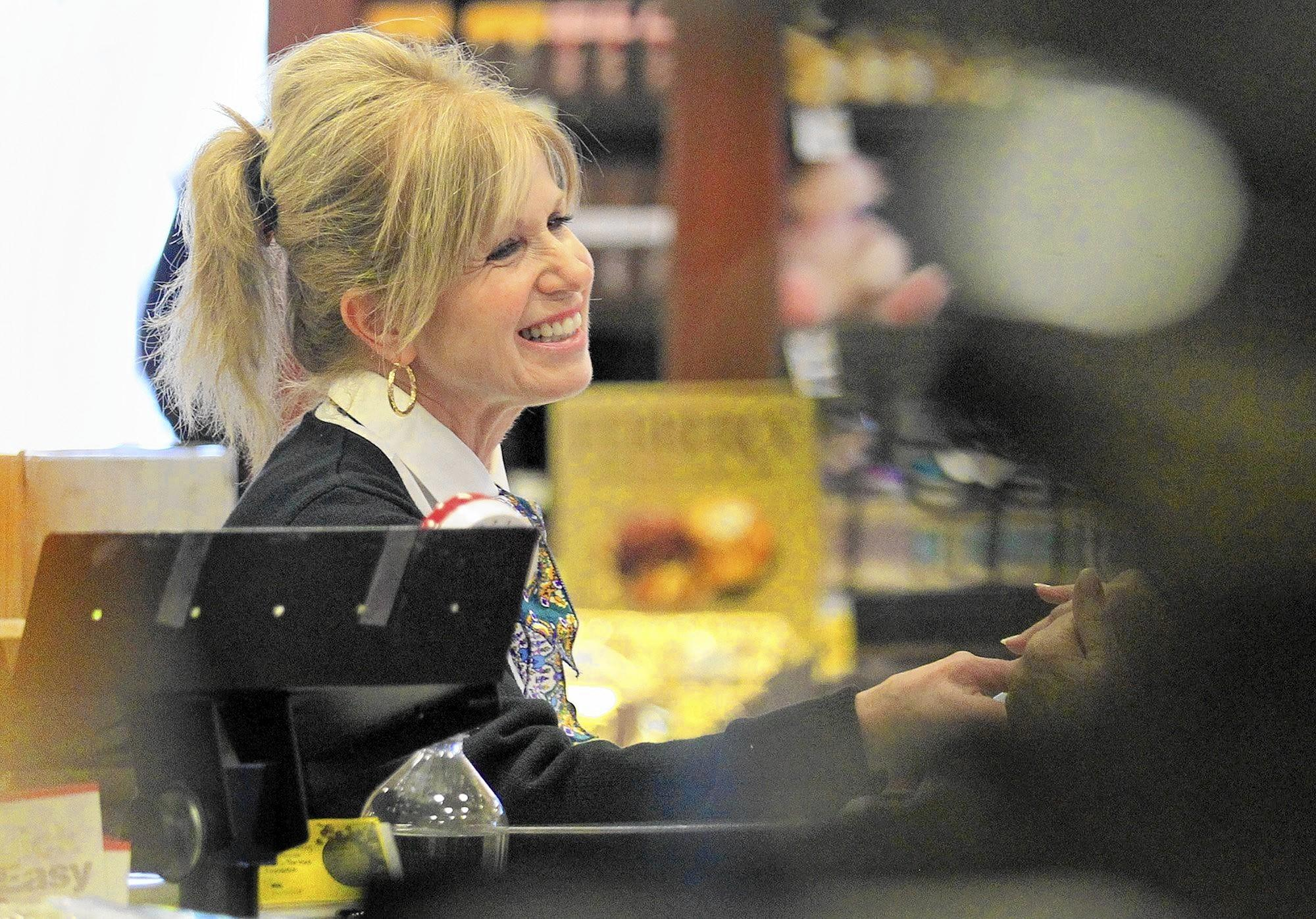 Cashier Linda Coughlin, of San Clemente, rings up a customer's groceries on her final workday at Pavilions in the Bayside Shopping Center in Newport Beach on Friday. Coughlin is retiring after 30 years of service at this Pavilions.