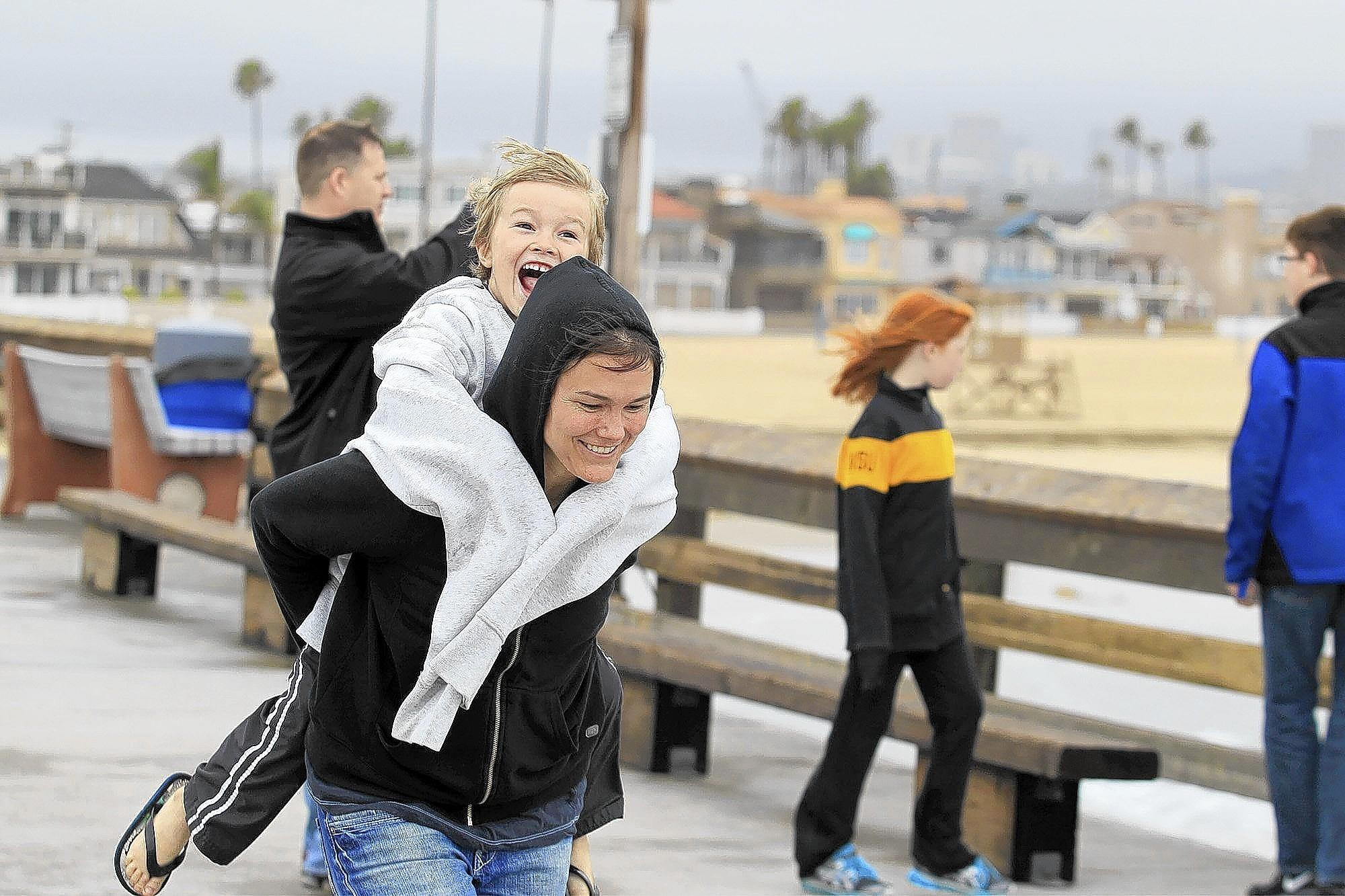 Alex Nef, 4, of Las Vegas holds on tight to his mother, Sally, as she runs toward the end of Newport Beach Pier on a cloudy and drizzly Friday afternoon.