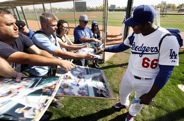 Fans get an autograph session with outfielder Yasiel Puig after the Dodgers completed a spring training workout last week at Camelback Ranch in Glendale, Ariz.