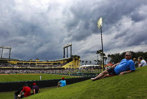 Mike Carrier from Detroit watches the Spring Training baseball game between the Atlanta Braves and the Detroit Tigers from the lawn behind the outfield on Wednesday, February 26, 2014 as storm clouds move in.
