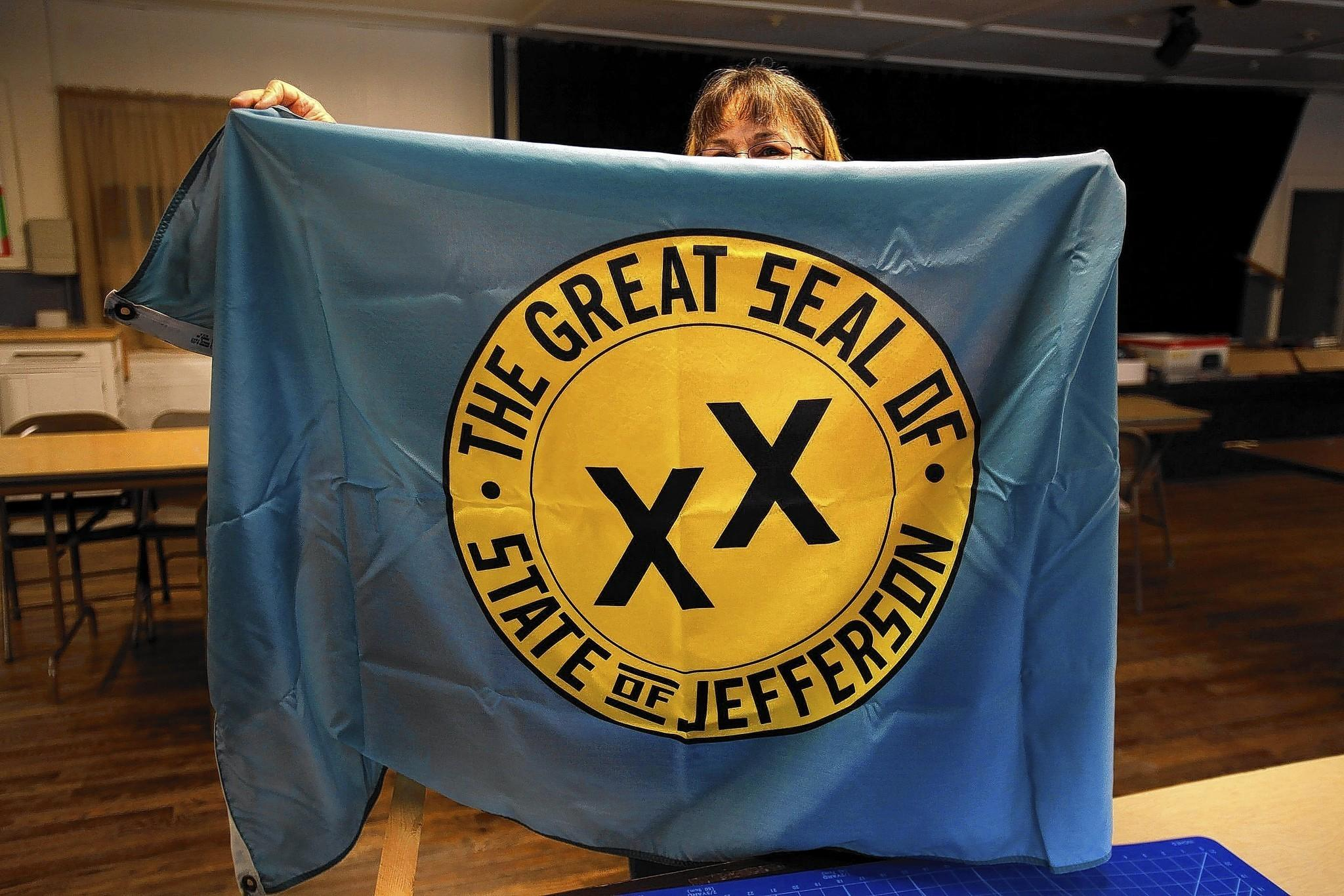 Molly Kelley of Klamath River holds up a State of Jefferson flag, which dates to a 1941 effort.