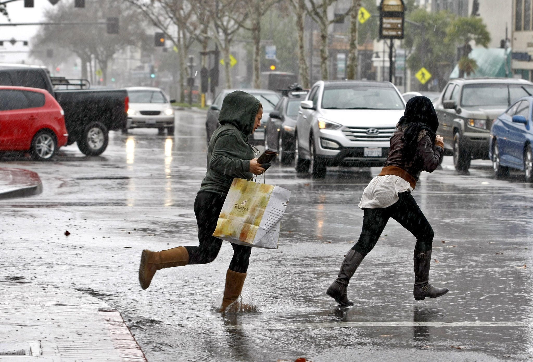 A couple of women dash across a flooded Brand Blvd. at California Ave. with the lunch from Panera Bread in Glendale on a rainy Friday, Feb. 28, 2014. The storm continues through the weekend.