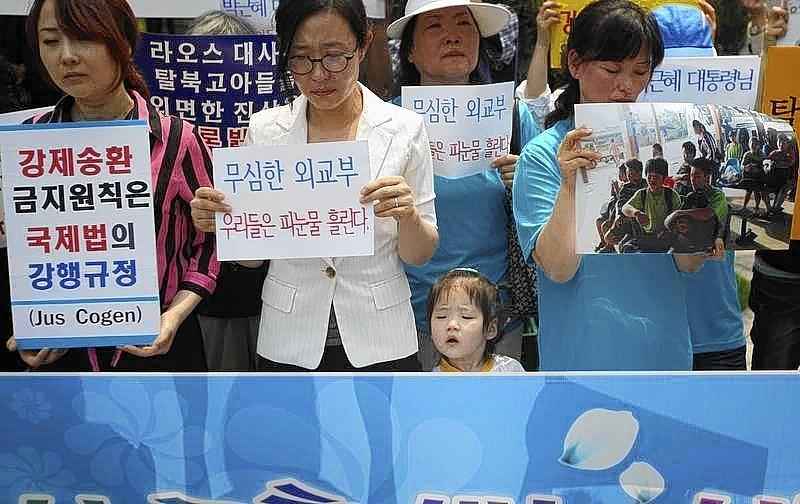 A young girl stands between protesters from a human rights group during a rally against what the U.N. believes is the recent repatriation of nine North Korean defectors from Laos, in front of the Foreign Ministry in Seoul in 2013.