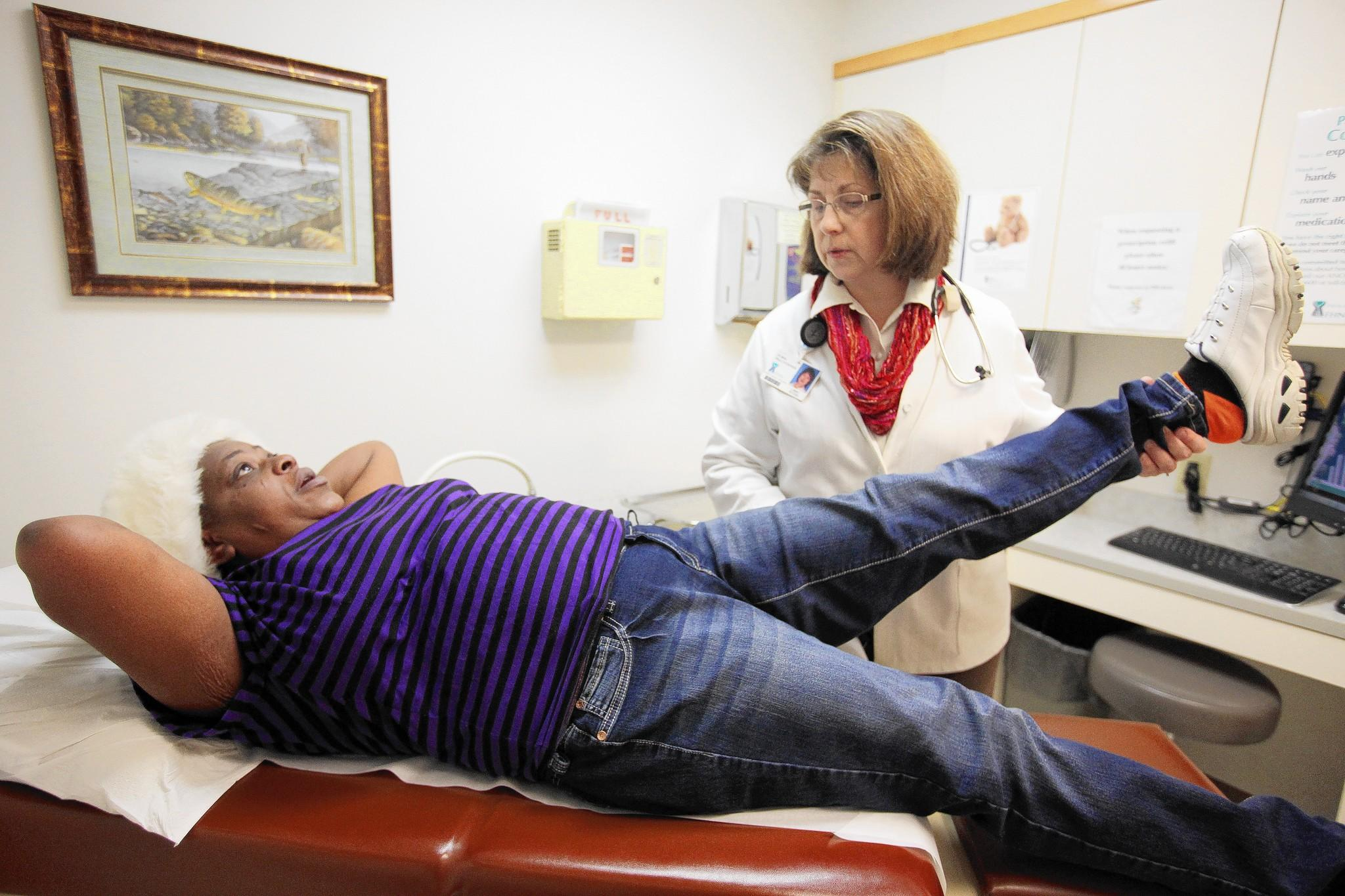 Libby Myers, right, a nurse practitioner at FHN Community Healthcare Center in Freeport, Ill., examines patient Zennetta Stuggis, who was being seen for chronic back pain. Stuggis, 49, recently enrolled in Obamacare.