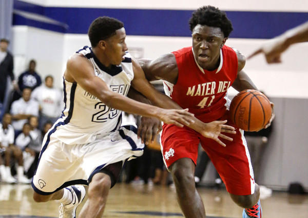 Mater Dei senior Stanley Johnson drives down the lane against Mayfair junior Kendall Small during a Southern Section Open Division playoff quarterfinal game on Friday night in Lakewood.