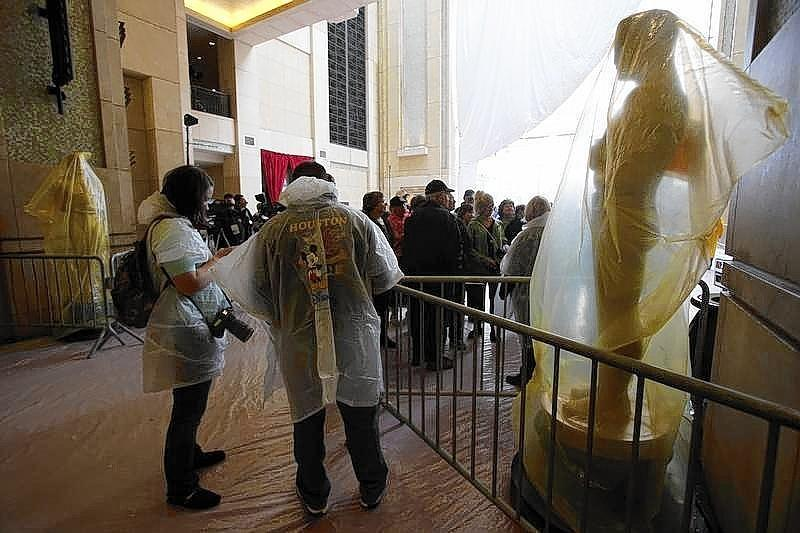 Tourists and photographers wearing rain gear stand next to Oscar statues covered with plastic during preparations for the 86th Academy Awards at the Dolby Theatre in Hollywood.