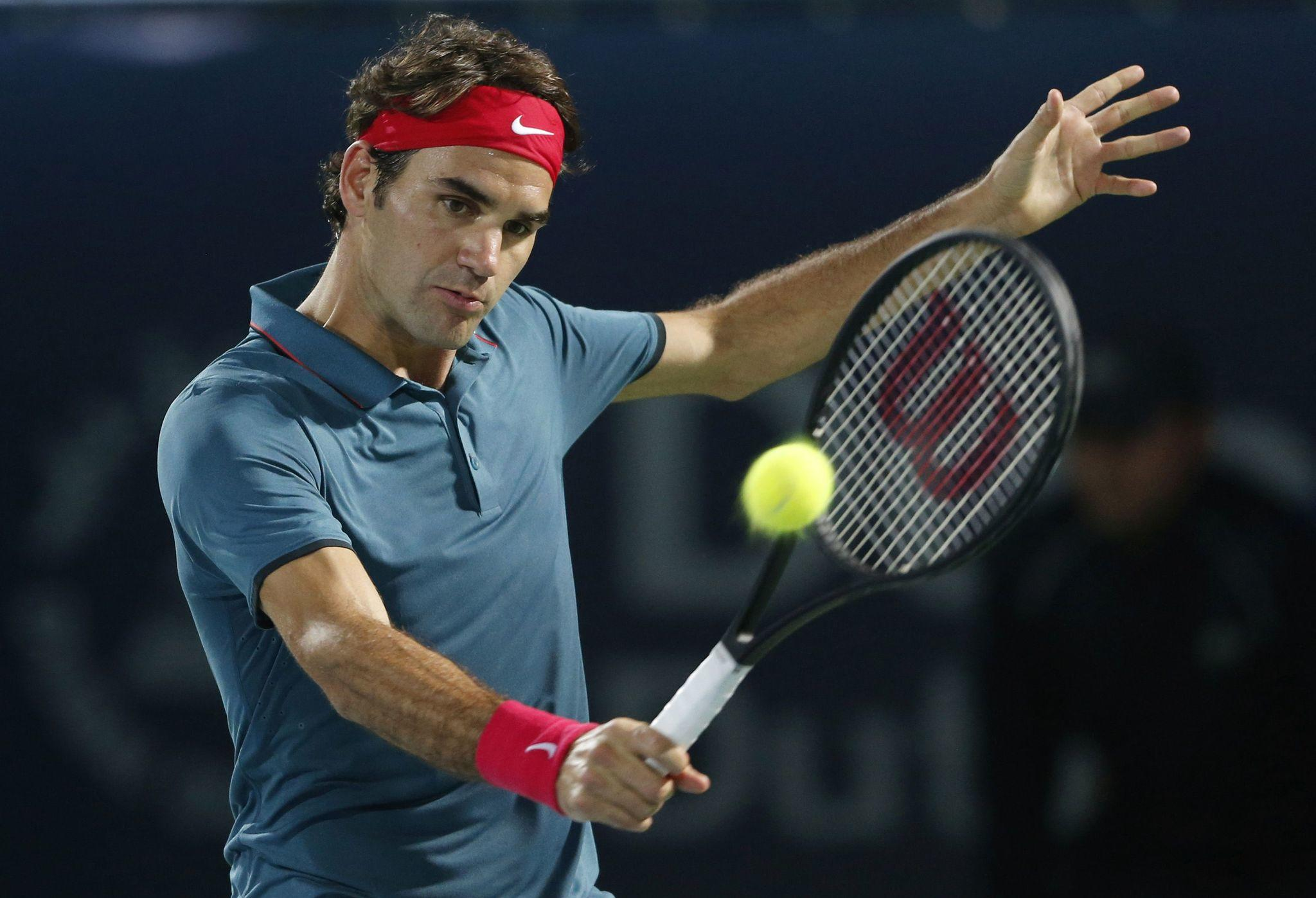 Roger Federer of Switzerland returns the ball to Tomas Berdych of the Czech Republic during their men's singles final match at the ATP Dubai Tennis Championships.