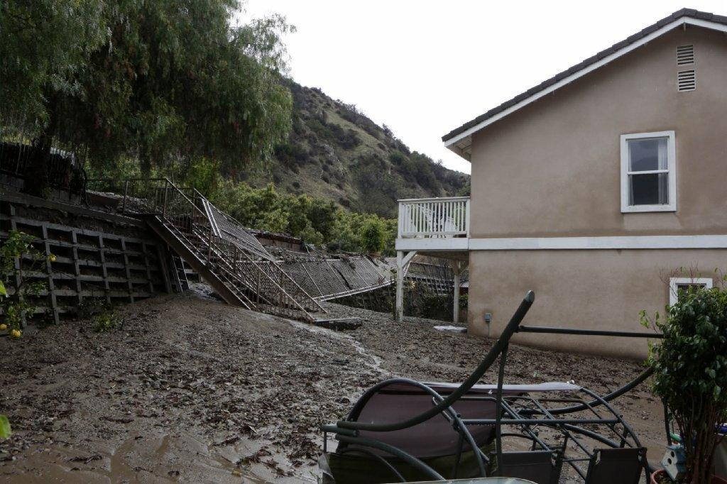 Mud oozes into the backyard of a home along Ridge View Drive in Azusa early Saturday.