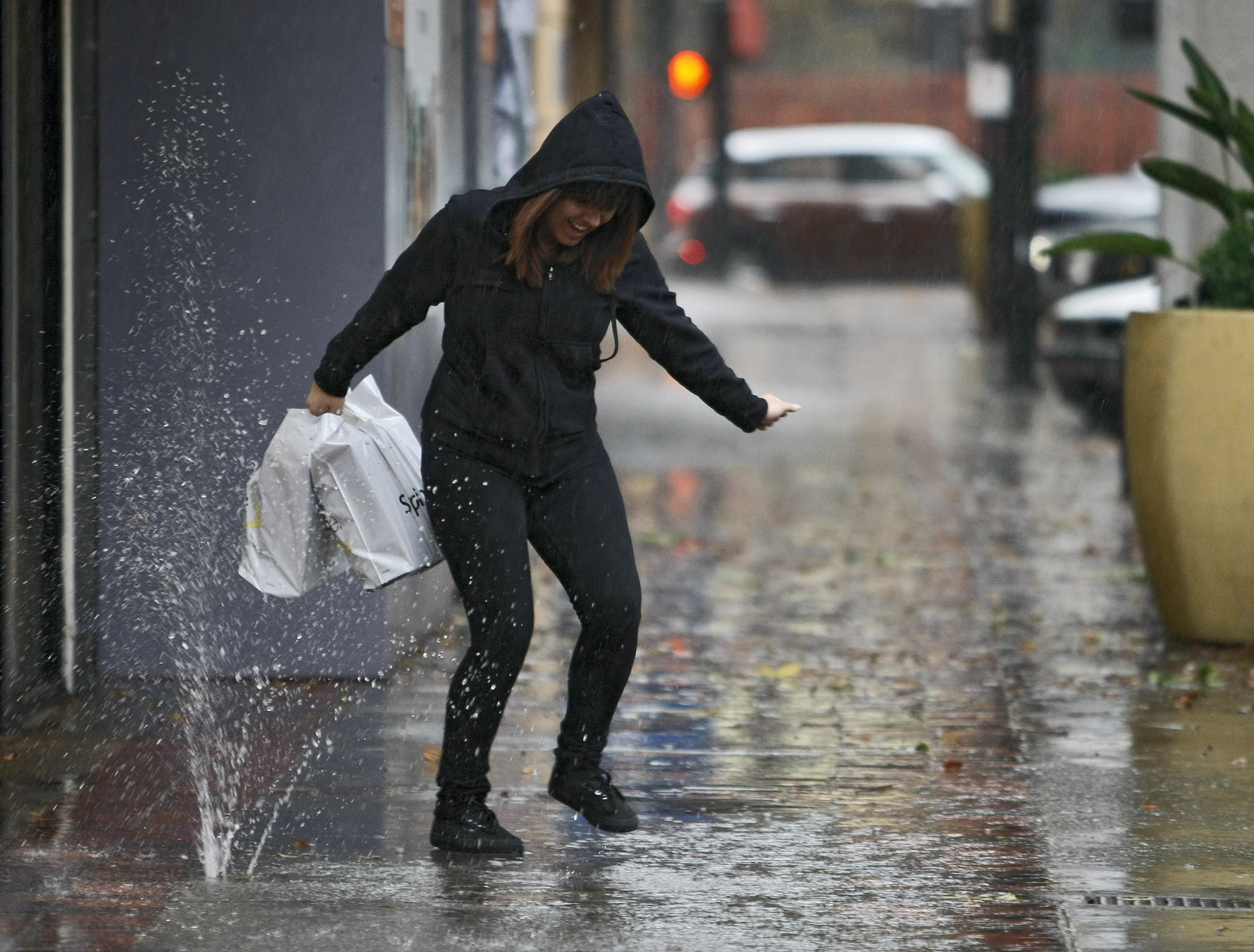 A woman tries to avoid the rain and water popping up from a drain on San Fernando Blvd. near Magnolia Blvd. in Burbank on Friday, Feb. 28, 2014. Rain is predicted through the weekend.