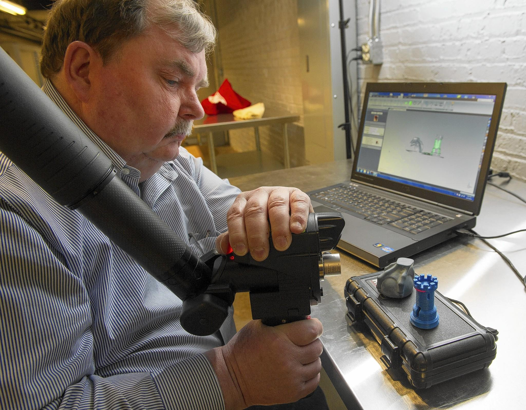 Kevin Collier demonstrates how a 3-D scanner is used to scan a chess piece, so it can be duplicated by a 3-D printer at America Makes, the 3-D innovation lab in Youngstown, Ohio. It was the first manufacturing lab set up by President Barack Obama and focuses exclusively on 3-D printing.