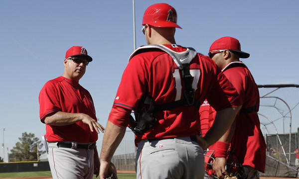 Angels Manager Mike Scioscia, left, speaks to his catchers during a spring-training practice session on Feb. 20. Scioscia understands the physical and mental demands his catchers face every game.