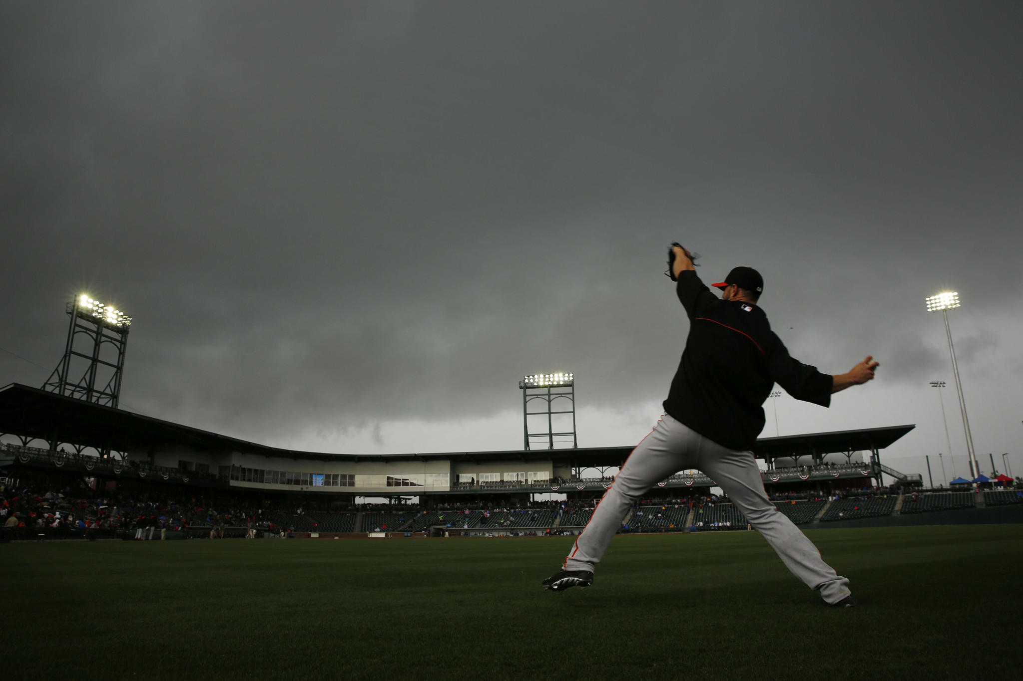 A San Francisco Giants pitcher warms up Saturday, March 1, 2014 in the outfield as clouds move in, causing a rain delay before a spring training game between the Cubs and Giants at Cubs Park in Mesa, Arizona. The game was eventually cancelled.