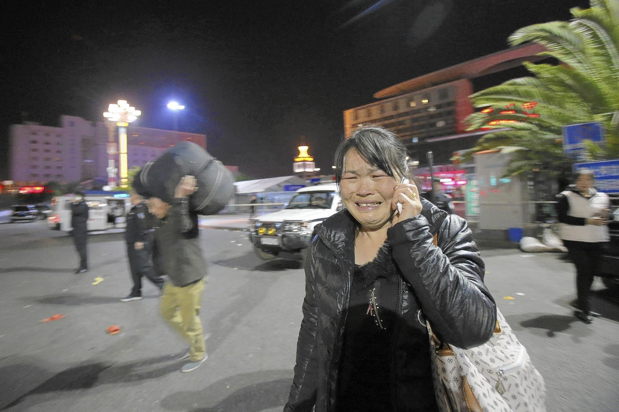 A woman reacts outside the railway station in Kunming, China, after the attack there by a group of knife-wielding assailants.