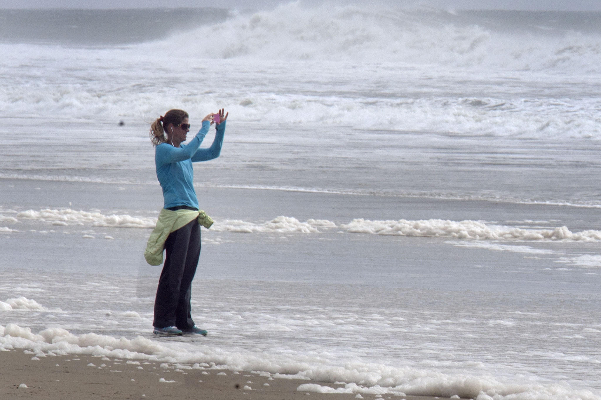 Socorro Hubbard takes pictures of the waves after her walk at Huntington Beach on Saturday. The storm-powered waves reached 8 to 12 feet.