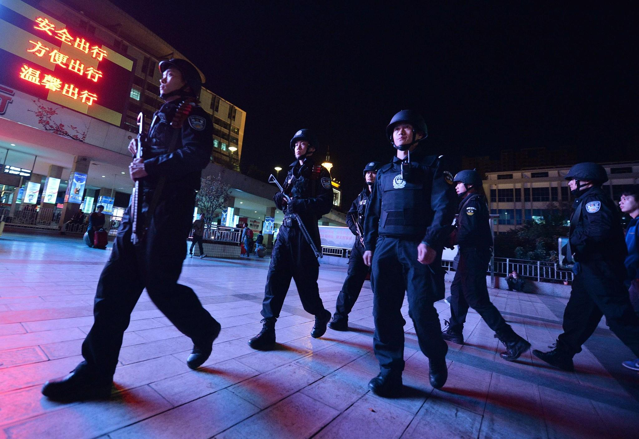 Armed police patrol the scene of a knife attack at the main train station in Kunming, China, in Yunnan Province on Sunday.
