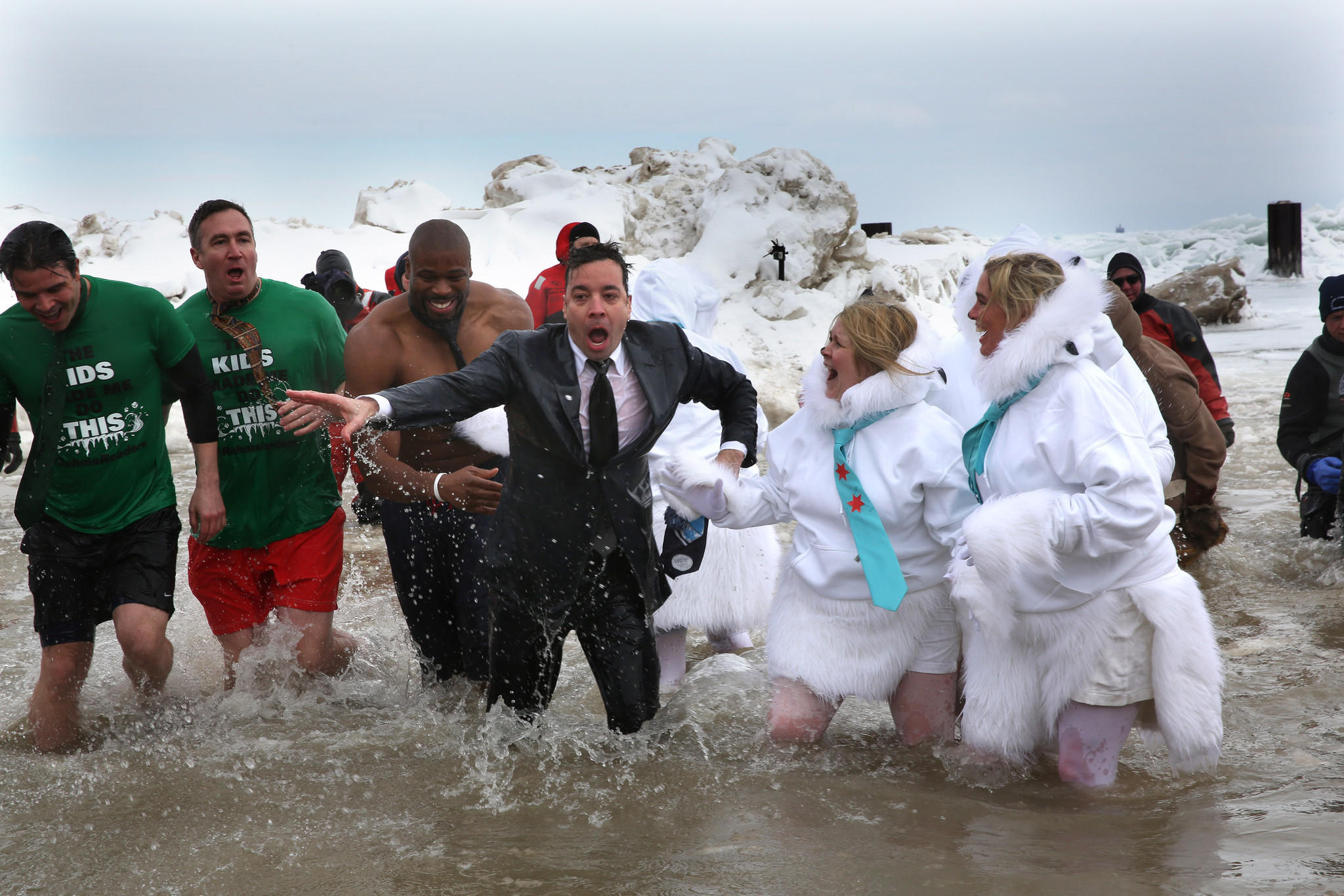 Suit-and-tie-clad Jimmy Fallon emerges from the water followed by former Bear Israel Idonije on Sunday after taking the Polar Plunge.