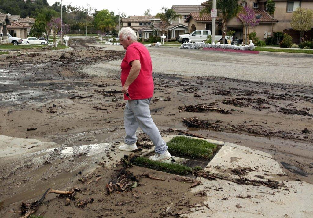 Azusa resident Ed Heinlein walks through the mud on the street in front of his home.