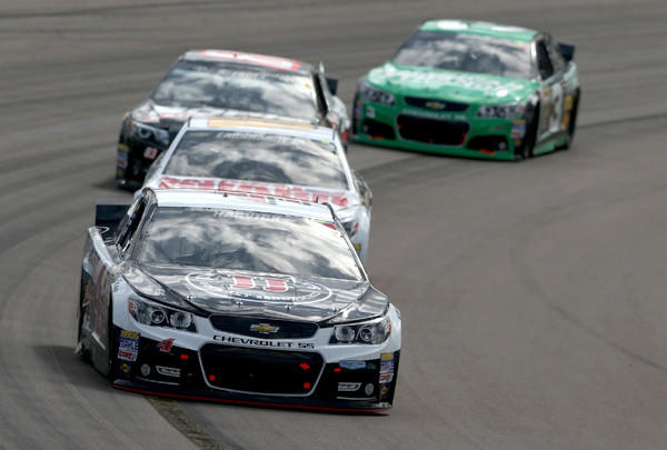 NASCAR driver Kevin Harvick guides his No. 4 Chevrolet around a corner as he leads a pack of cars in the Sprint Cup Series race on Sunday at Phoenix International Raceway.
