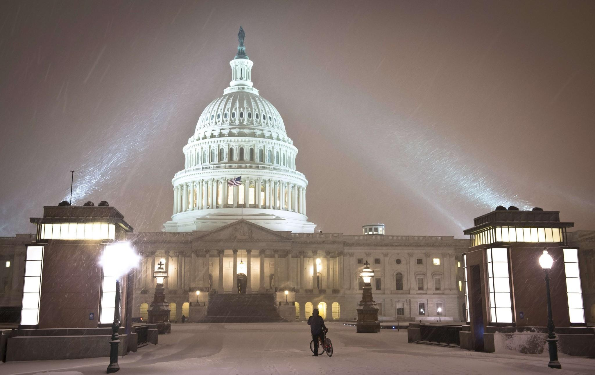 A cyclist looks at the US Congress building as a heavy snow storm hits Washington D.C. on February 13, 2014.