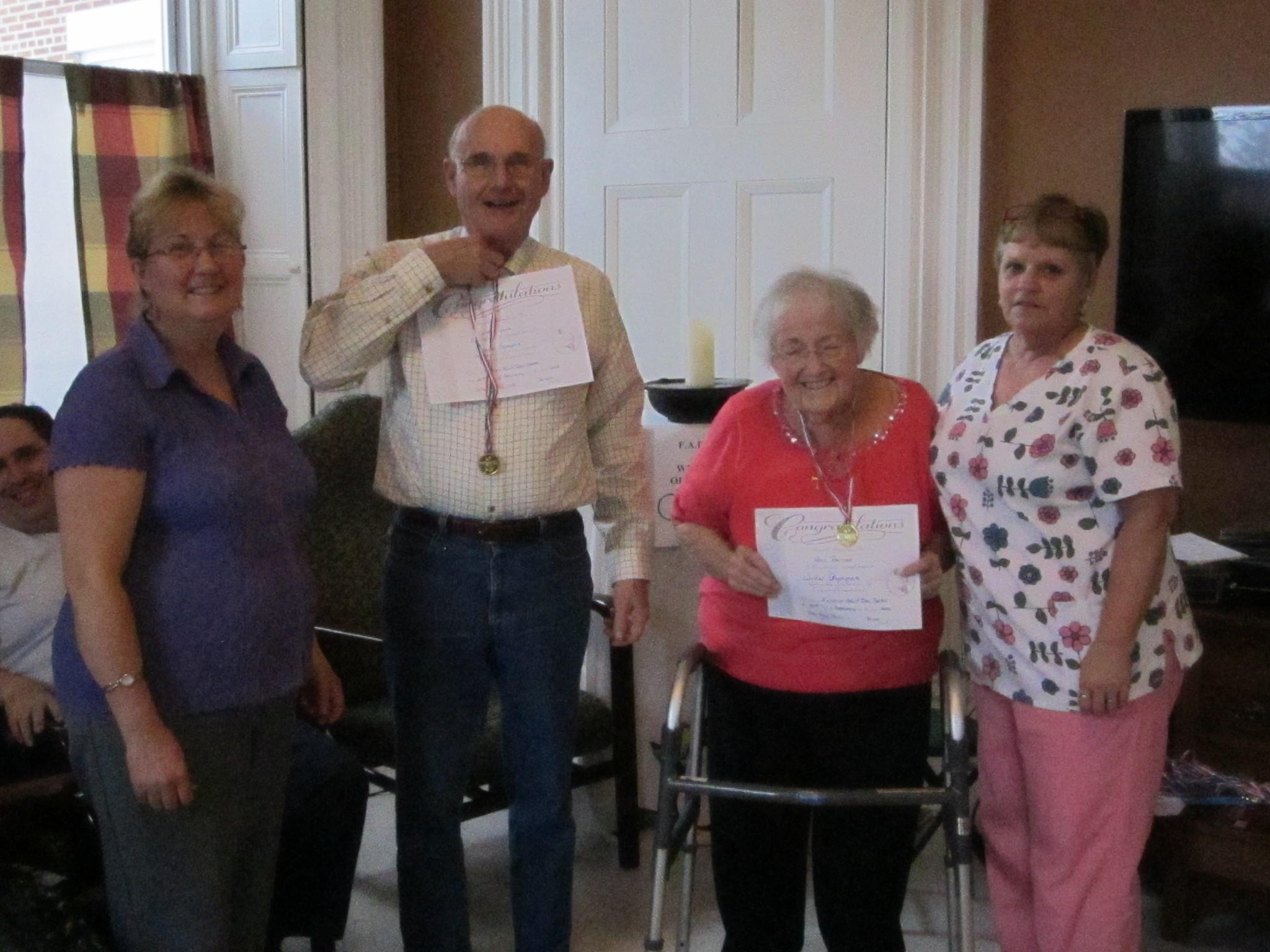 Laurie Bursztyn and Susan Reali award medals and certificates at the Felician Adult Day Center.
