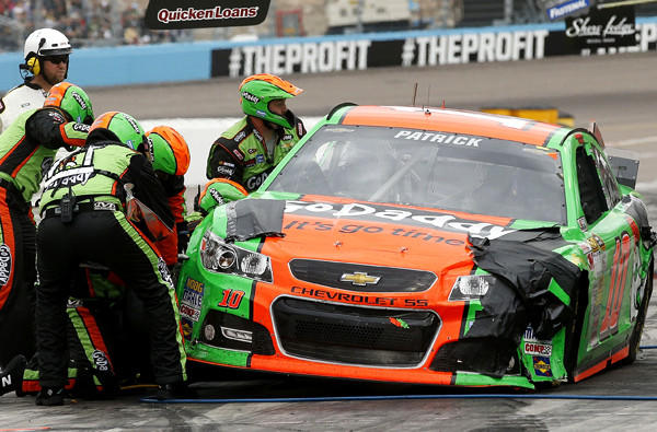 The crew of NASCAR driver Danica Patrick works on her damaged car during a pit stop Sunday at Phoenix International Raceway.