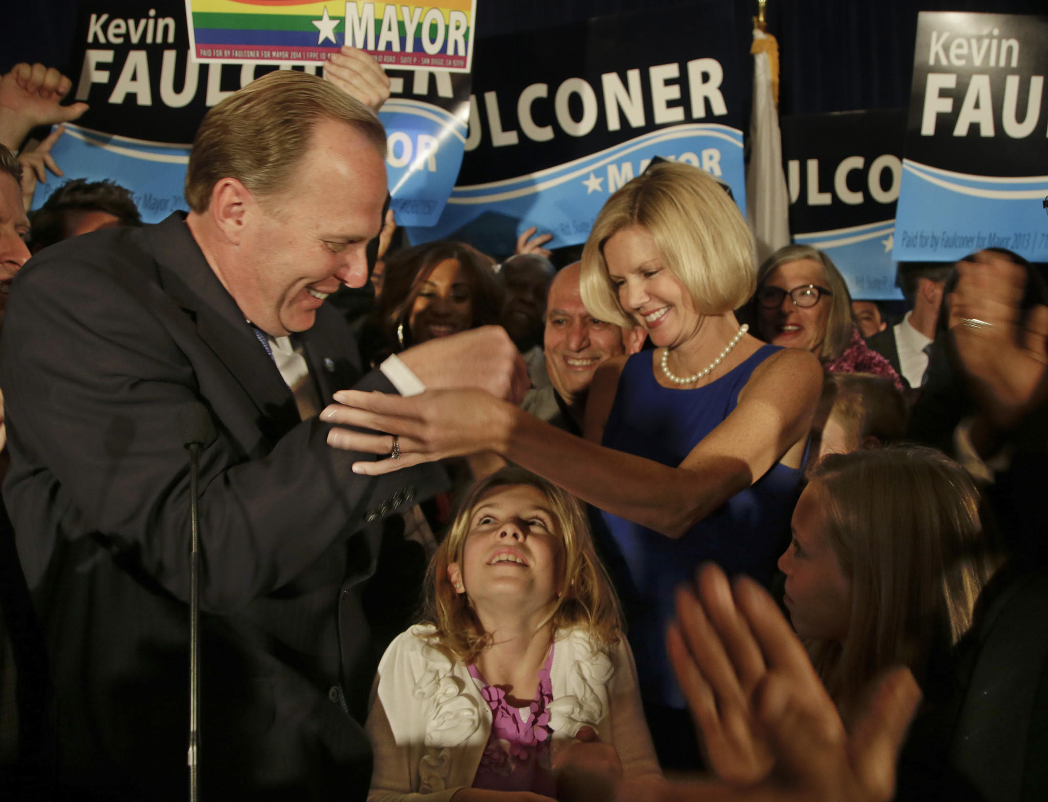 San Diego mayoral candidate Kevin Faulconer celebrates with his wife, Katherine, as their daughter looks up from below after Faulconer addressed his supporters at a rally last month in San Diego.