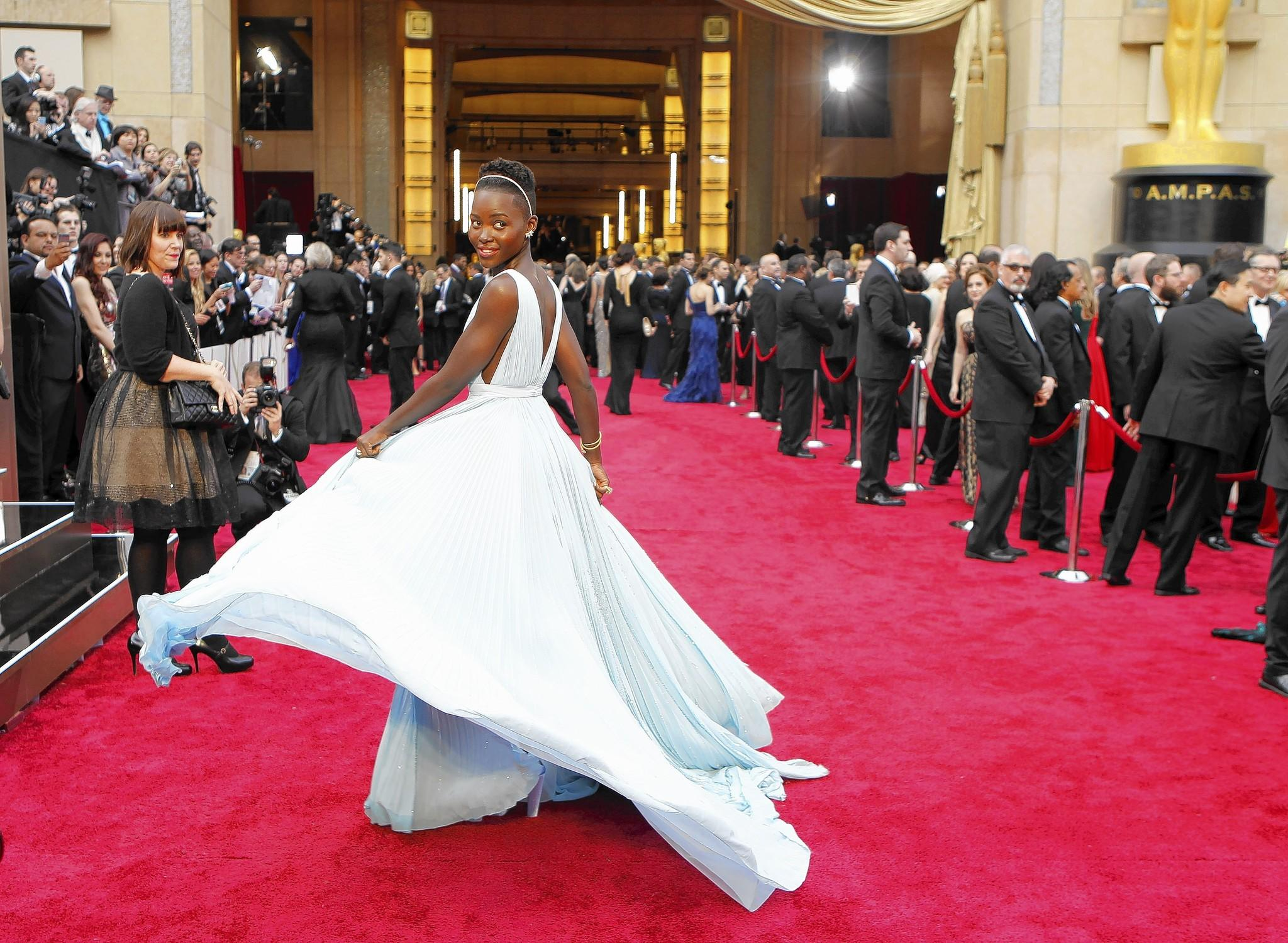 Lupita Nyong'o shines as this year's Academy Awards sweetheart in a silk georgette Prada gown in a shade of the lightest blue that the supporting actress Oscar winner said reminded her of home.
